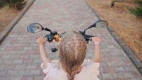 Opinión superior un niño con las coletas africanas que montan una vespa, vista posterior Reconstrucción alegre y activa almacen de metraje de vídeo