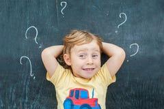 Opinión superior un pequeño muchacho rubio del niño con el signo de interrogación en la pizarra Concepto para la confusión, la re Foto de archivo