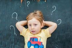 Opinión superior un pequeño muchacho rubio del niño con el signo de interrogación en la pizarra Concepto para la confusión, la re Foto de archivo libre de regalías