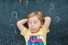 Opinión superior un pequeño muchacho rubio del niño con el signo de interrogación en la pizarra Concepto para la confusión, la re Imágenes de archivo libres de regalías