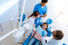 Opinión superior una muchacha agradable agradable que se sienta en la silla del dentista foto de archivo libre de regalías
