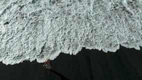 Opinión superior una muchacha que da un paseo a lo largo de una playa volcánica negra, Tenerife, islas Canarias, España almacen de metraje de vídeo