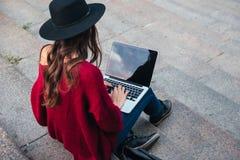 Opinión superior una mujer en sombrero que mecanografía en el ordenador portátil Fotografía de archivo libre de regalías