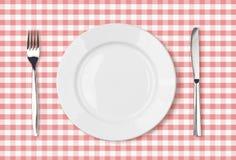 Opinión superior vacía de la placa de cena sobre mantel rosado de la comida campestre