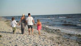 Opinión trasera cuatro miembros de familia feliz que caminan en la playa durante vacaciones de verano en la playa metrajes
