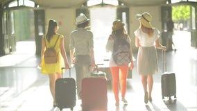 Opinión trasera cuatro muchachas bastante apuestas con los documentos, los boletos, y los bolsos grandes del viaje en manos en el almacen de video