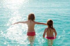 Opinión trasera de las muchachas de los niños en la playa en la puesta del sol Imagenes de archivo