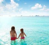 Opinión trasera de las muchachas de los niños en la playa en la puesta del sol Fotos de archivo