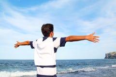 Opinión trasera de los brazos abiertos del adolescente del muchacho que mira el mar azul Imagenes de archivo