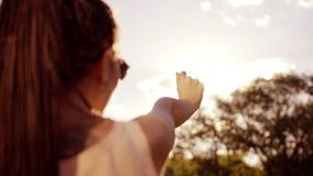Opinión trasera del primer una mujer que mira el sol y que se oculta del sol con su mano La mujer joven con teme almacen de video