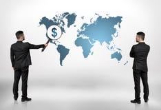 Opinión trasera dos hombres de negocios que miran el mapa del mundo con la muestra de dólar de agrandamiento de la lupa grande en Imagenes de archivo