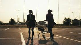 Opinión trasera dos muchachas elegantes atractivas que caminan en el estacionamiento del centro comercial Uno de ellos está soste metrajes