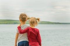 Opinión trasera dos niños del liitle, muchacho y muchacha, abrazando en un lago sh Fotos de archivo libres de regalías