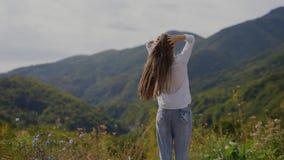 Opinión trasera el adolescente feliz encima de las montañas almacen de metraje de vídeo