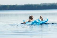 Opinión trasera el adolescente que se bate con sus brazos y que flota en lilo azul de la piscina al aire libre Imagenes de archivo