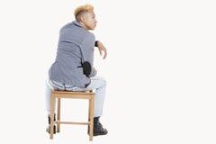 Opinión trasera el adolescente que se sienta en silla como él mira lejos sobre fondo gris Fotografía de archivo