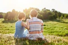 Opinión trasera el adolescente romántico y la muchacha que se sientan junto en la hierba verde que abraza teniendo charla que des Imagenes de archivo