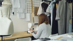 Opinión trasera el diseñador de la ropa de la mujer joven que trabaja con la máquina de coser que se sienta en el escritorio del  almacen de video