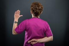 Opinión trasera el doctor mayor de la señora que toma juramento falso imagenes de archivo