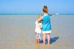 Opinión trasera el hermano y la hermana en la playa tropical Foto de archivo