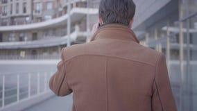 Opinión trasera el hombre acertado hermoso en capa marrón que camina en la calle de la ciudad que habla por el teléfono móvil Pai metrajes