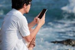 Opinión trasera el hombre asiático joven usando el teléfono elegante móvil en la orilla de mar Internet del concepto de las cosas fotografía de archivo