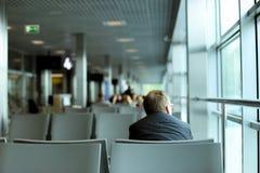 Opinión trasera el hombre caucásico que se sienta en sala de espera en el aeropuerto, el traje gris que lleva y los vidrios imagenes de archivo