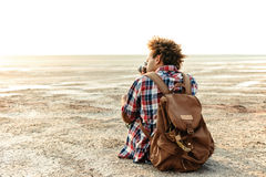 Opinión trasera el hombre con la mochila que toma las fotos en la playa Imagen de archivo