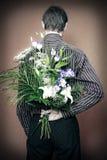 Opinión trasera el hombre con las flores Imagenes de archivo