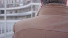 Opinión trasera el hombre confiado hermoso en capa marrón que camina en la calle de la ciudad que habla por el teléfono móvil Pai almacen de video