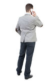 Opinión trasera el hombre de negocios en traje que habla en el teléfono móvil Foto de archivo