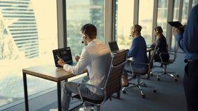 Opinión trasera el hombre de negocios joven hermoso y las mujeres de negocios hermosas en las auriculares que trabajan en oficina almacen de metraje de vídeo