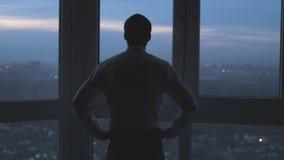 Opinión trasera el hombre de negocios pensativo que lleva un traje que mira fuera de la ventana panorámica C?mara lenta 3840x2160 almacen de metraje de vídeo