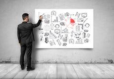 Opinión trasera el hombre de negocios que dibuja gráficos económicos en la lona blanca Fotografía de archivo libre de regalías