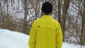 Opinión trasera el hombre en la situación amarilla de la capa de deportes en la colina en bosque del invierno almacen de video