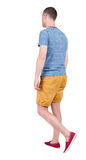 Opinión trasera el hombre hermoso que va en pantalones cortos individuo joven que recorre Fotografía de archivo libre de regalías