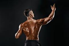 Opinión trasera el hombre irreconocible, músculos fuertes que presentan con los brazos para arriba Foto de archivo libre de regalías