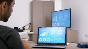 Opinión trasera el hombre que mira la pantalla de ordenador que comprueba datos de empresa en cartas animadas metrajes