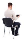 Opinión trasera el hombre que se sienta en silla y miradas en la pantalla Imagen de archivo libre de regalías