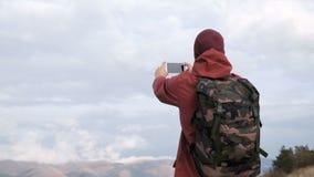 Opinión trasera el hombre que toma la foto del mar y de la montaña