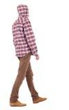 Opinión trasera el individuo que va en una camisa de tela escocesa con la capilla Foto de archivo libre de regalías