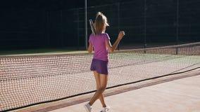 Opinión trasera el jugador de tenis de sexo femenino hermoso que golpea la bola a la tierra usando una estafa almacen de video