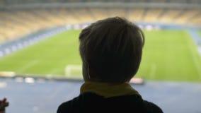 Opinión trasera el muchacho joven que mira el campo de fútbol, soñando para hacer futbolista almacen de video