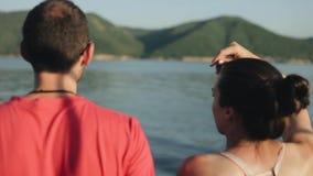 Opinión trasera el muchacho joven y la muchacha que disfrutan de la vista escénica del río y de las montañas Visión borrosa de la almacen de video