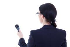 Opinión trasera el periodista de sexo femenino con el micrófono aislado en blanco Imagen de archivo libre de regalías