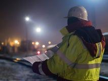 Opinión trasera el trabajador de construcción joven en casco en los dibujos de construcción de la lectura de la noche, impresione Imagen de archivo