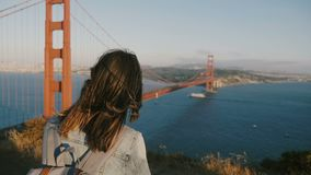 Opinión trasera hermosa la mujer turística joven con la mochila, pelo que sopla en el viento disfrutando de puesta del sol en pue almacen de metraje de vídeo