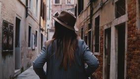 Opinión trasera la empresaria joven elegante confiada en sombrero y traje que camina a lo largo de la calle antigua estrecha en V almacen de video