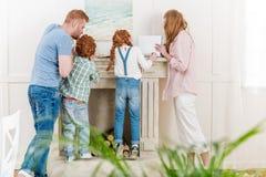 Opinión trasera la familia del pelirrojo con dos niños que se unen cerca de la chimenea y que leen las revistas Imagen de archivo