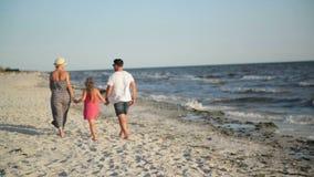 Opinión trasera la familia feliz con la pequeña hija que camina en la playa que lleva a cabo las manos durante vacaciones de vera almacen de metraje de vídeo